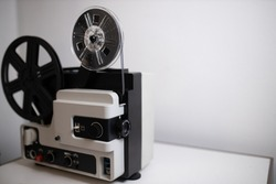Isolated 8mm projector. Antique video technology. Old retro machine for films. White background and filmstrip ready. Space for text. Film spool closeup