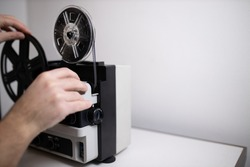 Isolated 8mm projector. Antique video technology. Old retro machine for films with human hands. Focusing with filmstrip ready