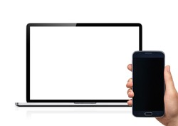 Isolated mockup of mobile phone and computer. Hand holding a samsung cellphone in front of a macbook.