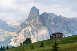 Isolated mountain hut surrounded by green meadows during summer. High Dolomite peaks of Italian Alps are visible in the background. Val Badia - South Tyrol, Italy