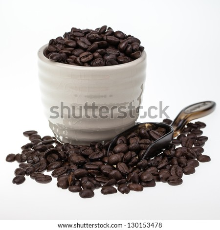 Isolated of coffee beans in white cup against white background