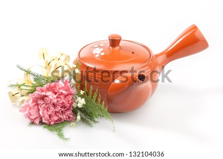 Isolated of pink bouquet placed near tea pot against white background