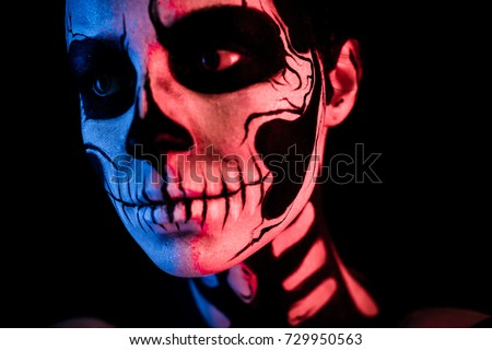 Stock Photo Isolated on black, closeup picture, toned red and blue, attractive young brunette caucasian woman with scull body art, grey eyes