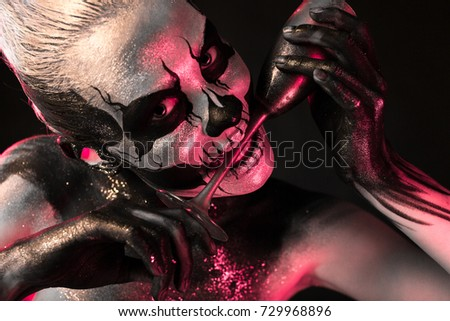 Stock Photo Isolated on black, closeup picture, toned red and white, beautiful young blonde caucasian woman with scull body art with wine glass in her teeth, grey eyes, look at camera