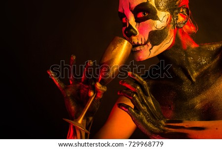 Stock Photo Isolated on black, closeup picture, toned red and yellow, beautiful young blonde caucasian woman with scull body art with wine glass in hand, grey eyes, drinks from glass, look at camera