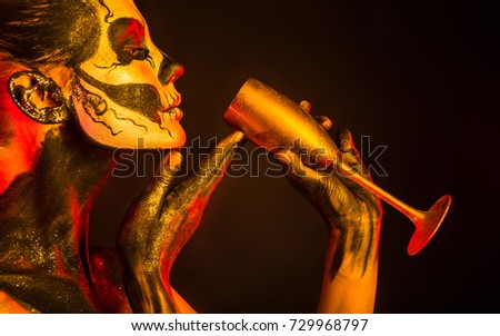 Stock Photo Isolated on black, closeup picture, toned red and yellow, beautiful young blonde caucasian woman with scull body art with wine glass in hand, grey eyes, drinks from glass with pleasure