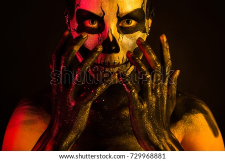 Stock Photo Isolated on black, closeup picture, toned red and yellow, beautiful young blonde caucasian woman with scull body art, grey eyes, look at camera, hands on face