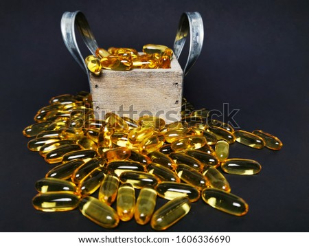 Isolated on black premium fish oil capsules in a wooden box with metal handles surrounded by lots of fish oil capsules.