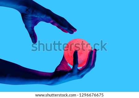 Isolated on blue background photo of man holding moon shape illuminated sphere. Surrealistic collage style, contemporary art element for design, posters and banners. Neon purple light. Pop inspiration