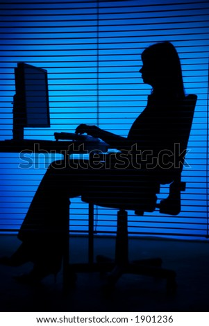 isolated on blue silhouette of woman working computer (focus on the blind; office unfocus)