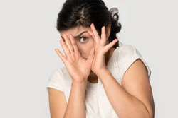 Isolated on grey studio background young indian afraid terrified woman hiding behind hands, trying to avoid something scared, making rejecting gesture, looking at camera, head shot close up portrait.