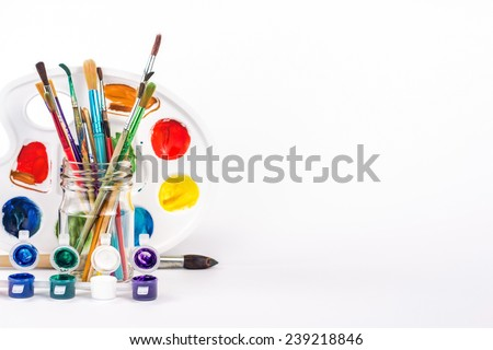 isolated paint palette and paints brushes in glass