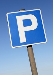 Isolated Parking Sign - Blue road sign with letter P on rectangular plate isolated against a blue sky.