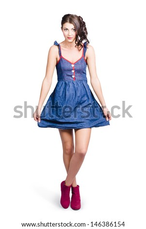 Isolated photo of a lovable eighties female pin-up curtseying in blue denim dress. 80s glamour style
