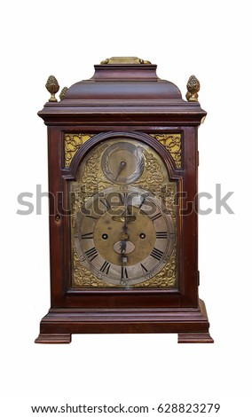 Isolated picture of an old table clock in wooden casing with beautiful metal dial #628823279