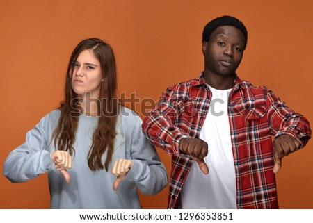 Isolated picture of dissatisfied frowning young European woman and dark skinned man grimacing and making thumbs down gesture, expressing disapproval or dislike, being disappointed with bad movie Foto stock ©