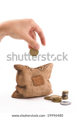 isolated piggy bank with coins and woman's hand