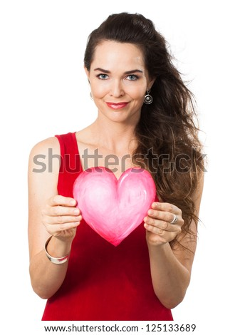Isolated portrait of a beautiful young woman in a red dress holding a red love heart.