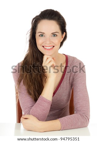 Isolated portrait of a happy young woman sitting at table