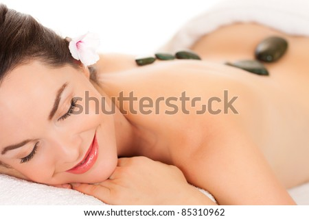 Isolated portrait of an attractive young woman getting a hot stone massage