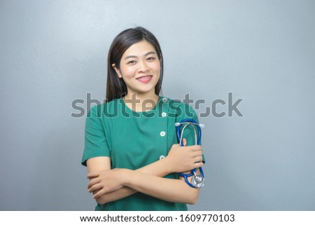 isolated portrait of asian female doctor a stethoscope with arms crossed the chest, representing checkup, diagnosing, health care, medical care, hospital care, wearing a green scrub and a stethoscope
