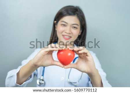 isolated portrait of asian female doctor holding a red love heart with both hands, representing checkup, diagnosing, health care, medical care, hospital care, wearing white lab coat and a stethoscope