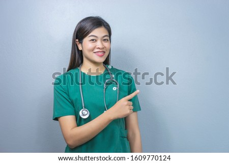 isolated portrait of asian female doctor wearing a green surgeon scrub and a stethoscope, pointing up at the side, represents checkup diagnosing, health care, medical care, hospital care, and surgery