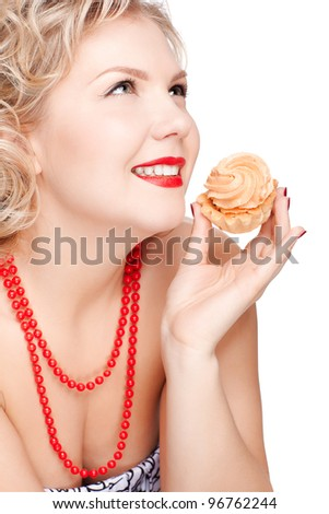 isolated portrait of beautiful smiling young blonde size plus woman model with tasty cream tart in hand