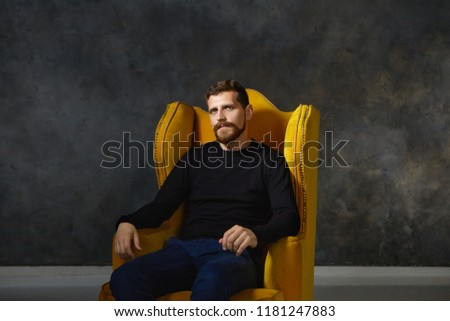 Isolated portrait of good looking elegant young European male with fuzzy trimmed beard and mustache wearing stylish black clothes posing in studio, sitting in comfortable yellow armchair alone
