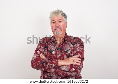 Isolated portrait of stylish  old senior man European bitting his mouth and looking worried and scared crossing arms, worry and doubt.