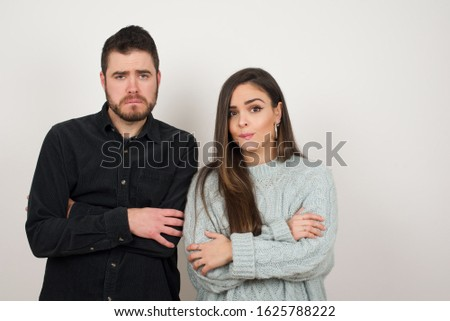 Isolated portrait of stylish young European couple bitting her mouth and looking worried and scared crossing arms, worry and doubt.