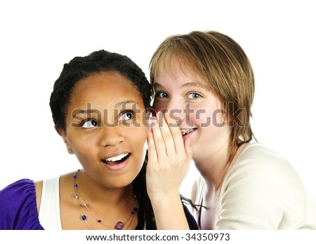 Isolated portrait of two diverse teenage girl friends whispering