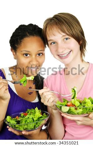 Isolated portrait of two teenage girls eating salad