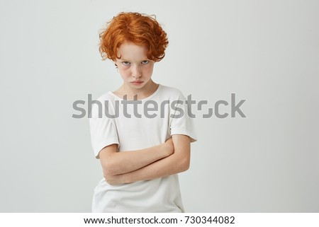 Isolated portrait of unhappy little kid with red curly hair and freckles being offended by teacher that gave bad mark for his answer.
