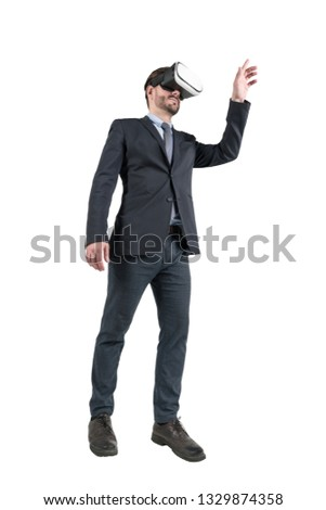 7e82cb1ccb9a Isolated portrait of young businessman wearing black suit and VR glasses  and interacting with virtual reality