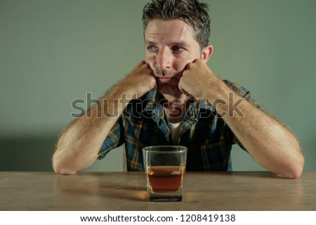 isolated portrait of young drunk addict and alcoholic man drinking whiskey glass intoxicated looking wasted resisting temptation to his alcohol addiction and abuse problem in alcoholism concept  #1208419138