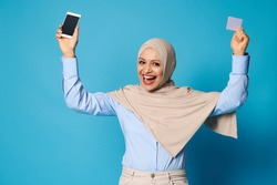 Isolated portrait on blue background of a happy smiling woman with covered head in hijab raising up her arms and holding mobile phone and plastic card in her hands