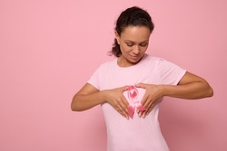 Isolated portrait on colored background of mixed race woman in pink t-shirt, putting her hands on her chest in shape of heart with a pink satin ribbon in the center. World Cancer Awareness Day.