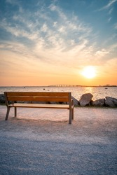 Isolated public bench at sunrise. Re island bridge in the background