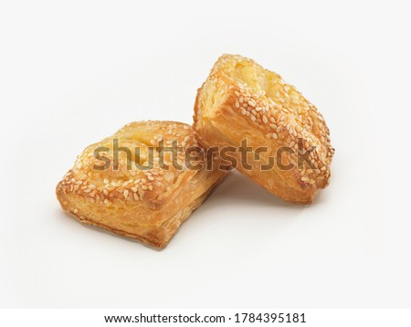 Isolated puff pastry with sesame and potato on a white background. A traditional Turkish pastry, puf borek. Greek pastry with sesame and potato on the white background.