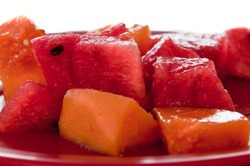 Isolated red plate with chunks of watermelon and papaya