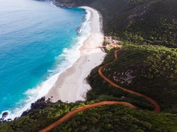 Isolated road down to Shelly Beach, Albany, Western Australia. The windy road takes you down to the isolated Shelly Beach with blue water and cliffs surrounding the beach. Shot aerially on a drone.
