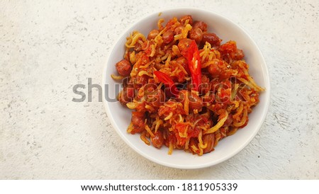 Isolated sambal teri kacang or fried anchovy and peanuts with hot and spicy chili sauce.  This chili surface looks noise and grainy. Stock fotó ©