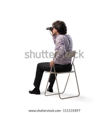 Isolated seated businessman using binoculars