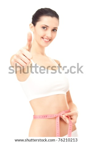 isolated shot,  healthy woman measuring her waistline and giving a thumbs up (focus on the thumb)