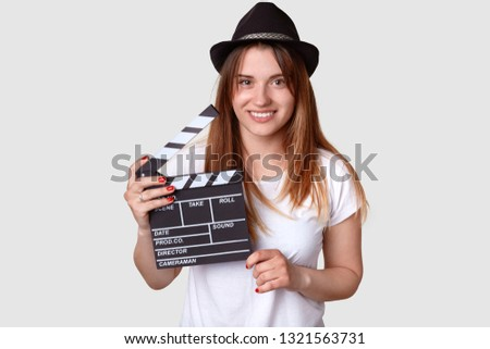 Isolated shot of cheerful woman director involved in sphere of cinematography, holds film clapper, dressed in casual t shirt and hat, isolated over white background. Film making and producing concept #1321563731
