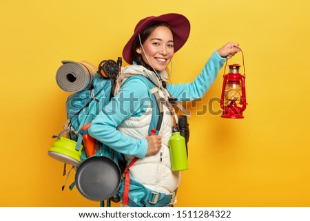 Isolated shot of cheerful woman trekker holds kerosene lamp, wears hat and casual wear, going have rest in forest, carries backpack, isolated over yellow stuido wall. People, trekking, hiking concept