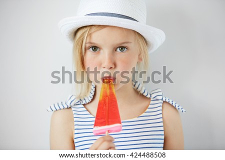 Isolated shot of cute little girl with green eyes and blonde hair, wearing white hat and striped dress, holding fruit ice cream. Portrait of Caucasian child licking popsicle and looking at the camera #424488508