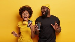Isolated shot of energized overjoyed dark skinned teenagers dance actively in rhythm of music, have spare time for drinking coffee, wear casual t shirts, spectacles, isolated over yellow studio wall