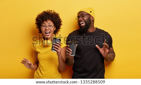 Isolated shot of energized overjoyed dark skinned teenagers dance actively in rhythm of music, have spare time for drinking coffee, wear casual t shirts, spectacles, isolated over yellow studio wall #1335288509